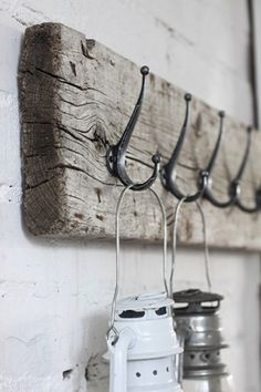 A weathered 2x4 and brass hooks makes an attractive hub in the mudroom. for entryway with lanterns