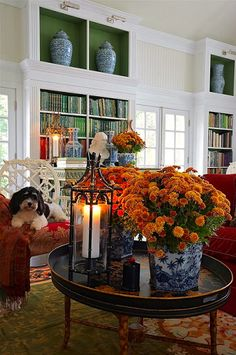 Carolyne Roehm's Connecticut family room all dressed up for autumn with candles and orange mums.