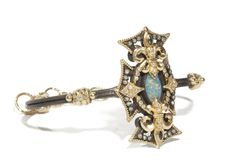 Midnight Fleur de Lis cross single shank cuff with marquis Boulder Opal, white diamonds, and blue sapphires with 18k yellow-gold saftey chain.
