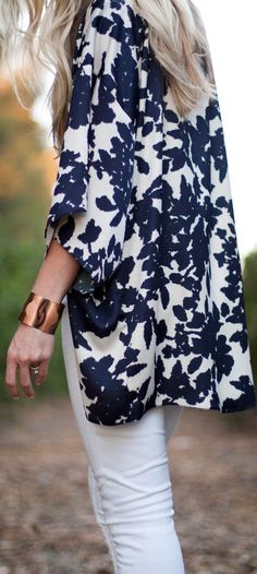 Blue and white floral kimono paired with white pants and a chunky bracelet.