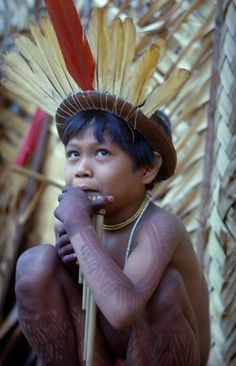Colombia, Vaupes Region, Tukano Tribe, Young Boy Playing Panpipes Outside Maloca Prior To A Festival. Painted With Deep Purple We Leaf Dye And Wearing Crown Of Red Macaw And Yellow Toucan Feathers : Stock Photo