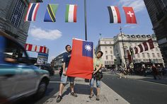 Two Taiwanese citizens hold up the flag of Taiwan at the retail district of Lower Regents Street. The International Olympic Committee decided in 1980 that Taiwan could only compete under the title Chinese Taipei and use a flag designed after the ruling.