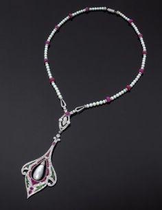 Important sautoir portant un pendentif à motif cachemire repercé serti de rubis calibrés et tsavorites dans un dessin floral. Au centre une perle fine de forme poire en pampille. Le tour de cou de perles fines, en légère chute, est rehaussé de boules de rubis et rondelles serties de diamants. La bélière losangique est ornée d'un diamant navette également en pampille dans un entourage de diamants brillantés (restaurations). Monture en platine et or gris 18 karats. Années 1925…
