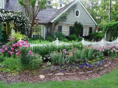 A white picket fence adds to the sweet setting of an Atlanta front yard with perennials and roses in bloom.