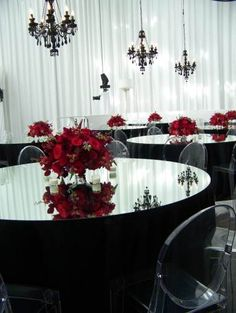 Black and red wedding theme. gorgeous black tableclothes, mirror table tops, red flower centerpieces, draping, and black chandeliers | I don't like the mirror tops, but I like how light it is, so I pinned it!