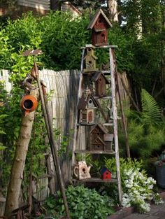 an old ladder displaying birdhouses