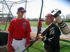 In this photo taken March 9, 2012, photographer Gregg Forwerck, right, talks with first-year Los Angeles Angels of Anaheim pitcher C.J. Wilson at Tempe Diablo Stadium in Tempe, Ariz. Since 1989, Forwerck has been taking pictures of professional baseball players for the New York-based Topps Co. that appear on many of the baseball cards.