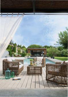 Un rideau en voilage pour créer un coin détente sur la terrasse. Salon de jardin en osier et piscine en fond // Net curtain on the terrace, swimming pool