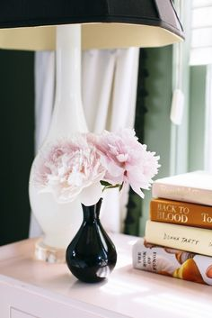 Pink peonies on a bedside table with stacked books.