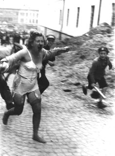 Young boys with wooden clubs chase a battered and bloodied Jewish woman during the Lviv pogroms, Ukraine, 1941
