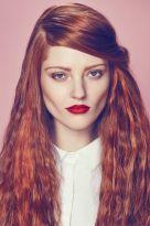 Gewelltes, langes Haar in Rot mit Seitenscheitel und hellen Highlights