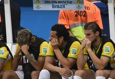 (L-R) Brazil's injured forward Neymar, Brazil's forward Fred and Brazil's defender Henrique react on the bench at the end of the third place play-off football match between Brazil and Netherlands during the 2014 FIFA World Cup at the National Stadium in Brasilia on July 12, 2014. Netherlands won 3-0.