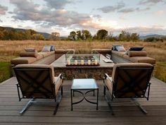 Four separate gas units comprise the modern fire pit design of HGTV Dream Home The Utah limestone-clad column is topped in a surface of limestone. A clear glass surround protects gas flames while contributing to the deck's open fire experience.