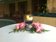 Rubber duckie baby shower centerpiece with pink flowers for a girl.