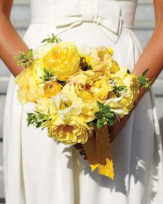 The bridal bouquet will be loose, naturally-shaped bouquets of yellow garden roses, yellow ranunculus, white anemones with black centers, ivory spray roses and hints of gray dusty miller and greenery.  The bridesmaids will carry similar bouquets, but we will use yellow spray roses instead of ivory so their's will have a little less white....
