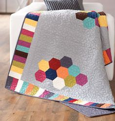 Out of Bounds from Quilting Quickly Fall 2013 is a throw size quilt that features clusters of brightly colored hexagons set against a modern gray background. Quilt by Natalie Earnheart.