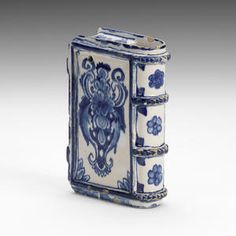 An English delftware hand warmer, circa 1680-1700  Probably London, modelled in the form of a book, the spine with four horizontal straps in high relief, the boards outlined around the edge in a similar manner and secured by two delicate fasteners, painted in blue on both sides with a formal floral and foliate motif, the spine with simple florets