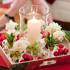 In Miniature        A pillar candle surrounded by several smaller accents creates an elegant display. The candle inside the clear glass hurricane stands tall amidst small vessels filled with water and a single flower or sprig of foliage. Red metallic florist's picks and loose silver ornaments add color and sparkle.
