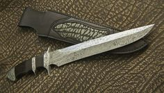 Subhilt by David Broadwell. Delbert Ealy damascus. Ray Cover engraving on stainless fittings. Sheath by NB Designs a subsidiary of Broadwell Studios.
