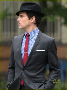 Gray suit, blue striped button-up, red tie, fedora. (Matt Bomer looking sharp.)