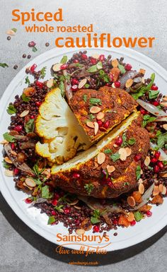 This spiced whole roasted cauliflower is vegetarian and vegan friendly main course. Coriander, cumin, tumeric and cinnamon turn a simple cauliflower into a roast dinner centrepiece. This is vegan winter comfort food that's also 3 of your 5 a day. Serve on a bed of green lentils and sprinkle with toasted almonds, pomegranate seeds, parsley and mint.