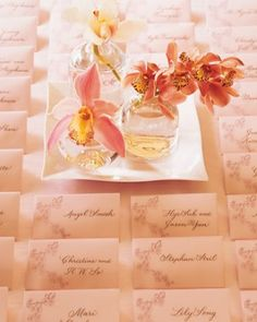Among these rows of seating cards sit pink, white, and plum-colored cymbidium orchids in glass vases resting on a porcelain dish