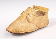1775-85, One of the few 18th century examples of children's footwear preserved in the collection, this infant's shoe features an appealing two-tone yellow color scheme to add interest to the simple form. The cut derives from the adult latchet-tie style, but has the added feature of an ankle strap. Although not a feature of adult footwear at the time, ankle straps are common on children's shoes, as they secure the shoe more surely to wriggling feet.