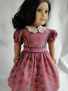This dress features a crocheted collar, made from a cream colored thread . This collar buttons in the front with a small black button and