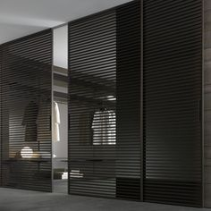 Modern walk-in dressing room with black semi-transparent sliding doors