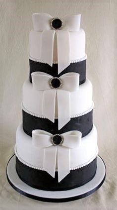 Wedding cake embellished with sculptured white bows and brooch