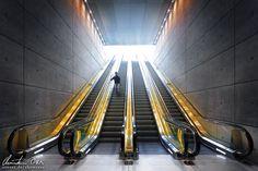 Mann auf Rolltreppe in einer modernen Station in Malmö, Schweden.