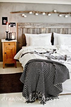 white + wood + grey bedroom // draumesider I like the piece of wood with it looks to be lights hanging off them.