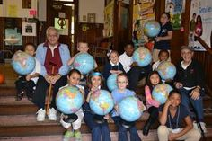 Brothers Al, right, and Ed Smith join with Watson Elementary School students after donating a globe to each of the school's classrooms.