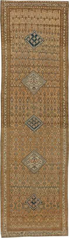 This circa-1920 antique Persian Malayer runner rug features an intricate all-over design of repeating diamond shapes containing linear abstractions in shades of inky blue, peach and brown, against a beige field densely patterned with small geometric motifs. Antique rugs from #dorisleslieblau