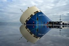 The cargo ship Modern Express is reflected in water as it lists at a mooring in the port of Bilbao, Spain