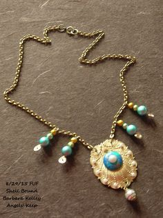 """FUF for 8/28/15, and August Challenge. Simple artisan beach themed necklace. 100% of the components are from b'sue boutiques.com, except for the 20"""" vintage brass chain.  Raw brass seashell medallion, trimmed with tiny faux pearls, a round center vintage cabochon in aqua, gold, and blue topped with a round faux pearl cabochon.  Caged faux pearl dangle.  Handcrafted brass wire spiral dangles with graduated glass Spectra beads in aqua, green and gold.  Barbara Kelley, Angels' Keep"""