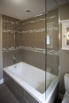 A tempered glass wall provides support for the shower curtain rod and permits natural light to flow into the room. - This is what I'm hoping for.