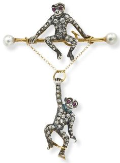 An antique diamond and ruby monkey brooch. Designed as a rose-cut diamond monkey seated on a bar set with pearl terminals, suspending another similarly set monkey, both with circularcut ruby eyes, length 5 cm, c. 1860, mounted in silver and gold.ruby eyes, length 5 cm, c. 1860, mounted in silver and gold. Please note that the pearls have not been tested for natural origin. Via Phillips.
