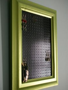 This is a wood frame painted with a funky apple green metallic paint. The surface is finished with a protective glossy coat. The hanging surface is a black enameled aluminium sheet metal.