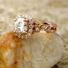 Elegant, vintage-style ring in rose gold with moissanite & diamonds. Gem specs: 1.00 ct Forever Brilliant moissanite, 6.5 mm round cut, comes with C.O.A. We have many other kinds of gem stones available. 34 diamonds of excellent quality with 0.31 ct total weight. Diamonds are no less