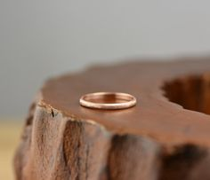 A simple hand crafted 14k rose gold half round ring band. The band measures 2mm in width x 1mm in thickness. Half round means that the outside