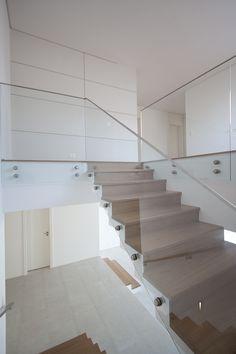 Escada em madeira freijó com guarda-corpo em vidro. Projeto por Mikaelian Freitas Arquitetura, Residência em Alphaville.