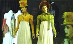 Image: Persuasion display case, cream dresses with gold coloured or green sleeved bodices and matching bonnets, as worn in the film