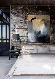 The beaten-copper tiles of the Cape Town waterfront apartment's bedroom reflect light from the windows opposite. The untitled painting above the bed is by Ulrich Binedell, while the bed and nightstands are custom Cécile & Boyd designs. Photo by Frank Features/Elsa Young
