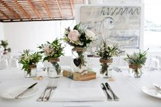 Great decoration for the table for signing certificates- old books with flowers in glass jars placed on top