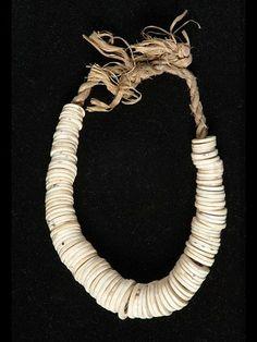 Collier-monnaie formée de rondelles de coquillages enfilées dans une cordelette de fibres végétales tressées
