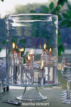 At outdoor parties, guests will notice lighting from the moment they arrive. An easy, inexpensive solution to provide light while outdoor entertaining is to gather clear bottles and fill them with lamp oil and wicks. Arrange them under a large hurricane for protection and set on a sturdy glass cake stand. #marthastewart #diydecor #diyprojects #diyideas #hobby Summer Centerpieces, Table Centerpieces, Modern Centerpieces, Solar Powered Lights, Solar Lights, Empty Wine Bottles, Apothecary Bottles, Hurricane Oil Lamps, Diy Tisch
