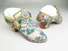 Pair of woman's shoes, England, first half 18th century. Cream silk brocaded with floral motifs, green silk ribbon, curved heel, pointed toe.