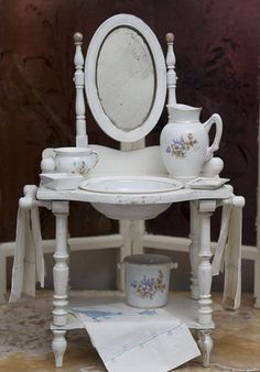 """19""""h (48 cm). Painted white wooden toilette table with towel bars, under-shelf and attached hinged mirror, removable porcelain bowl, handled pitcher, soap dish, pot, bucket. The set including 3 linen towels with blue embroidery. 18 1/2"""" (47 cm) tall. France,circa 1890. Ruby Lane SOLD  $750.00"""