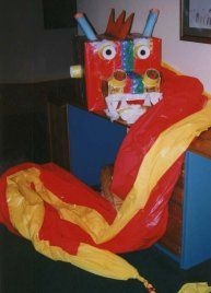 Make a Vietnamese Dragon Parade using cardboard boxes and red and yellow plastic tablecloths.